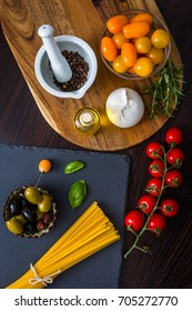 Variety of fresh cherry tomatoes on the table, pasty, cheese, spices, olives, top view.