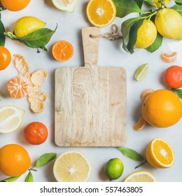 Variety of fresh citrus fruit for making juice or smoothie and wooden chopping board over light grey marble background, top view, copy space, square crop. Healthy eating, vitamin, clean eating concept