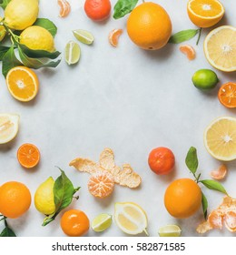 Variety of fresh citrus fruit for making juice or smoothie over light grey marble table background, top view, copy space, square crop. Healthy eating, vitamin, detox, diet food, clean eating concept