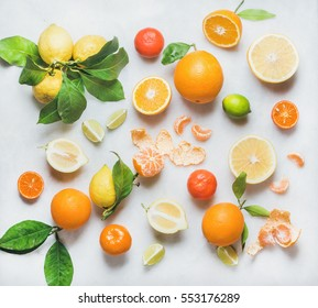 Variety of fresh citrus fruits for making juice or smoothie over light grey marble table background, top view. Healthy eating, vitamin, detox, diet food, clean eating concept