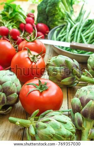 Variety of Fresh Organic Vegetables Artichokes Green Beans Tomatoes Red Radish Broccoli on Wood Garden Kitchen