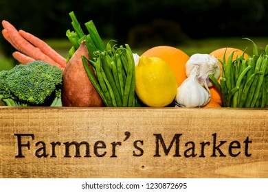 Variety of fresh produce in a Farmer's Market wooden box.