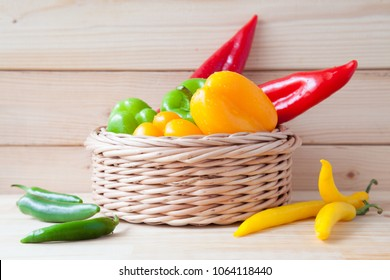 Variety of fresh ripe vegetables in a basket on wooden table