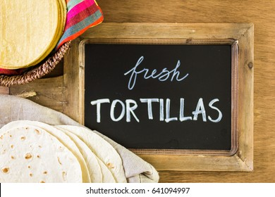 Variety of fresh tortillas on a wood background.
