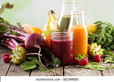 Variety of fresh vegetable and fruit juices in bottles and mason jar.