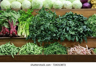 Variety of fresh vegetables cabbage, green leaves horta, spinach, celery, green beans, beets on the counter in the grocery store Athens, Greece. Horizontal.
