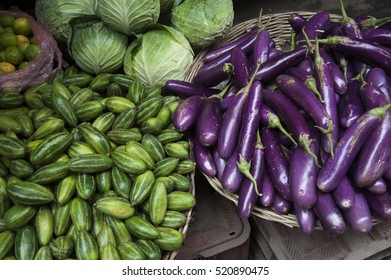Variety of fresh vegetables and fruit for sale on the streets of Kathmandu, Nepal including purple zucchini and mini cucumbers