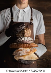 Variety of freshly baked breads in a young bakers hands. Hipster nordic baker with rye, wholewheat and white bread.