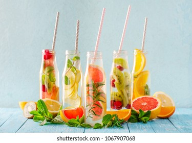 Variety of fruit infused detox water in small bottles. Set of refreshing summer drinks. Healthy diet eating concept.