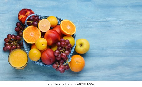 Variety of fruits on the blue wooden table, top view.