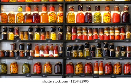 Variety glass jars of homemade pickled or fermented  colorful vegetables and jams on the shelves in food market. Fermented food concept.