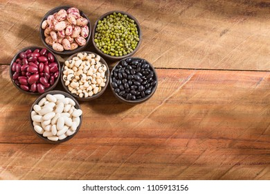 Variety of grains - pinto, black, mung, white, and chickpeas on wooden background