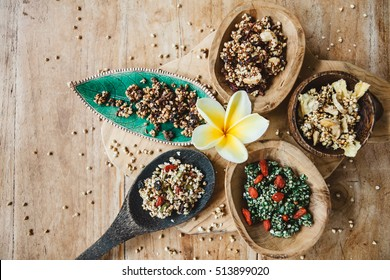 Variety of green buckwheat granola with berries and dries fruits in wooden spoons, healthy mindful eating