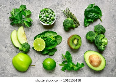 Variety of green fruits and vegetables  on a grey concrete, stone or slate background.Top view .