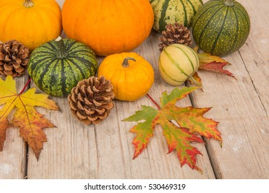 Variety of green and orange pumpkins, pine apples and leaves seen from above on a white washed scaffolding wooden plank background