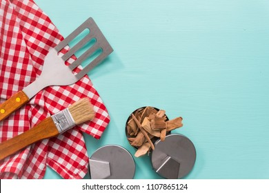 Variety of grilling tools on blue background.