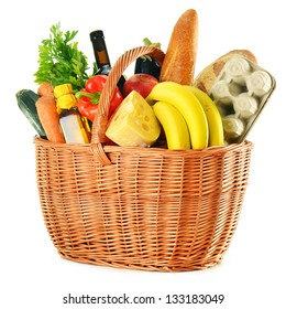 Variety of grocery products in wicker basket isolated on white
