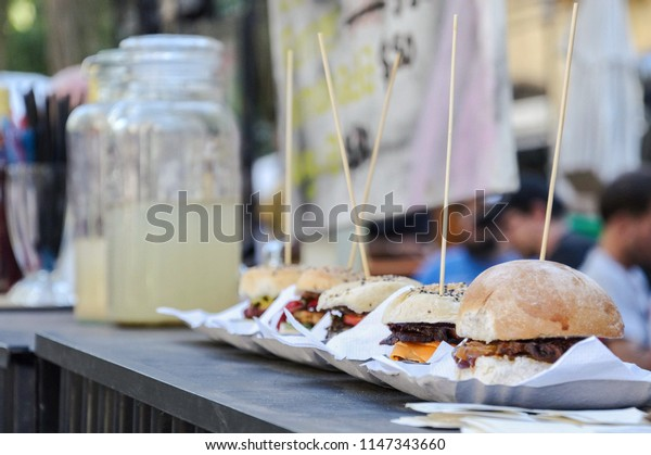 Variety of hamburgers on cardboard plate with toothpick stuck in the middle on wooden counter