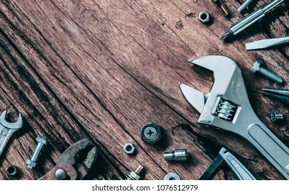 Variety Handy Tools on grunge wooden background. Top view close up of wrenches, Pliers, screwdriver, nuts and bolts on wood background with copy space for your text. Worker's, Labor's day background.