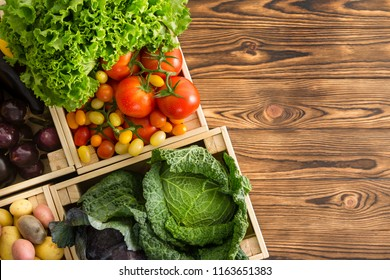 Variety of healthy fresh vegetables in boxes displayed on a wooden table wooden table at an organic farmers market viewed top down with copy space