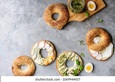 Variety of homemade bagels with sesame seeds, cream cheese, pesto sauce, eggs, radish, herbs served on crumpled paper with ingredients above over grey texture background. Top view, space.