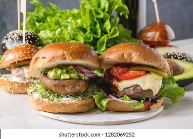 Variety of homemade classic, vegan and mini burgers in wheat and black buns with beef and veal cutlets, portobello mushroom, avocado on white ceramic board over white marble table. With glass of cola.