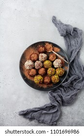 Variety of homemade dark chocolate truffles with cocoa powder, pistachios, almonds in light gray background texture. Top view, copy space.