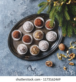 Variety of homemade dark chocolate truffles with cocoa powder, coconut, walnuts as Christmas gift on tray with fir tree, Christmas decorations above over blue background. Top view, space. Square image