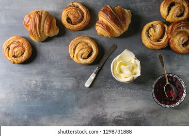 Variety of homemade puff pastry buns cinnamon rolls and croissant served with jam, butter as breakfast over blue texture background. Flat lay, space