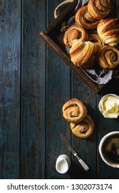 Variety of homemade puff pastry buns cinnamon rolls and croissant served with coffee cup, jam, butter as breakfast over dark plank wooden background. Flat lay, space