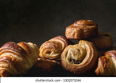 Variety of homemade puff pastry buns cinnamon rolls and croissant. Dark still life. Close up