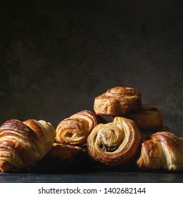 Variety of homemade puff pastry buns cinnamon rolls and croissant on wooden table. Dark still life. Copy space. Square image
