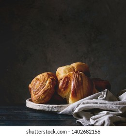 Variety of homemade puff pastry buns cinnamon rolls and croissant in ceramic plate on wooden table. Dark still life. Copy space. Square image