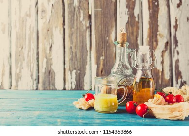 Variety of homemade sauces and salad dressings in jars including oil, vinegar, mustard dressing for salad. Space for text.