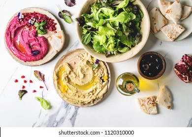 Variety of homemade traditional and beetroot spread hummus with pine nuts, olive oil, pomegranate served on ceramic plates with pita bread and green salad on white marble background. Flat lay, space.