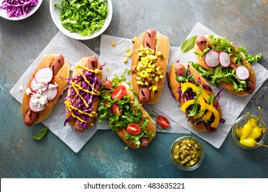 Variety of hot dogs with healthy vegetable garnishes and condiments