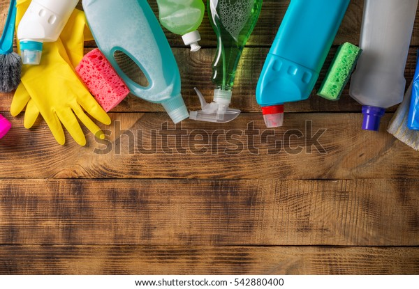 Variety house cleaning product on wood table with copy space, top view
