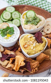 Variety of hummus and cream cheese and vegetable chips for dipping