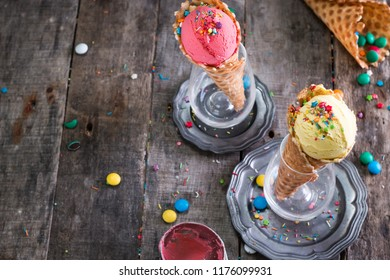 Variety of ice cream scoops in cones with mint, vanilla and strawberry