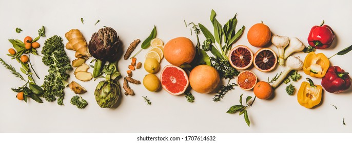 Variety of immunity boosting foods. Flat-lay of ginger, turmeric, kale, artichoke, citrus fruit, herbs, garlic, pepper over white background, top view. Healthy, raw vegan virus defeating ingredients