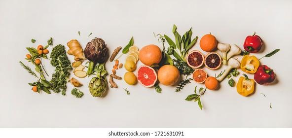 Variety of immunity boosting foods. Flat-lay of ginger, turmeric, kale, artichoke, citrus fruit, herbs, garlic, pepper over white background, top view. Healthy, vegan virus defeating ingredients