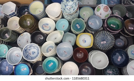 A variety of intricately designed colorful Japanese bowls and dinnerware for sale and with price tags at a Tokyo market.