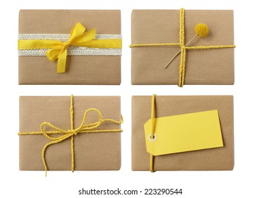 Variety of isolated neutral presents with yellow bow and blank gift tag