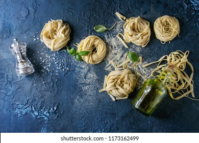 Variety of italian homemade raw uncooked pasta spaghetti and tagliatelle with basil leaves, olive oil, salt, pepper, semolina flour over dark blue texture background. Flat lay, copy space