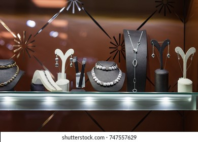 Variety of jewelry in store window. Rings, bracelets, earrings and necklaces on stands for sale