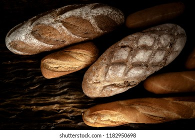 variety kinds of bread on wooden plank in dark tone