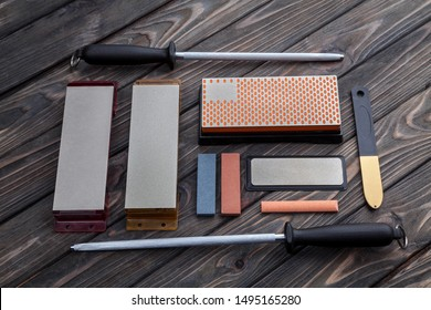 A variety of knife sharpeners. Sharpening stones and devices on a wooden background. Grinding stones