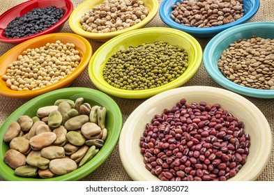 variety of legumes (fava bean, mung bean, soy, green lentils, adzuki, black, pinto, chickpea) in colorful ceramic bowls on canvas