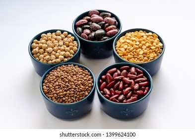 A variety of legumes. Lentils, chickpeas, peas and beans in blue bowls on a white background. Close-up