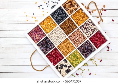 Variety of legumes, range, in a white wooden box with cells, peas, green peas, corn, beans, lentils. Top view.